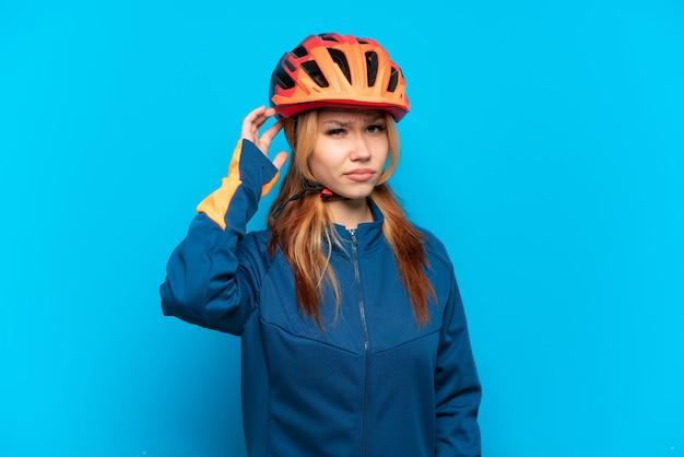 疑いを持って青い背景で隔離の若いサイクリストの女の子