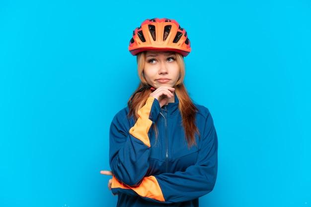 Девушка молодой велосипедист, изолированные на синем фоне, сомневаясь