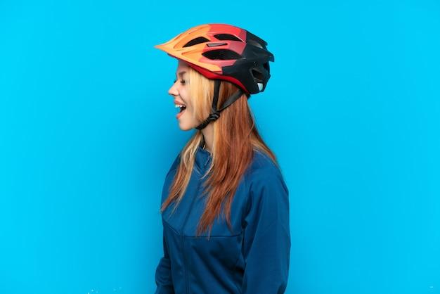 Молодая велосипедистка изолирована на синем фоне, смеясь в боковом положении