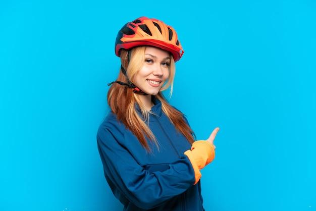 後ろ向きの青い背景で隔離の若いサイクリストの女の子
