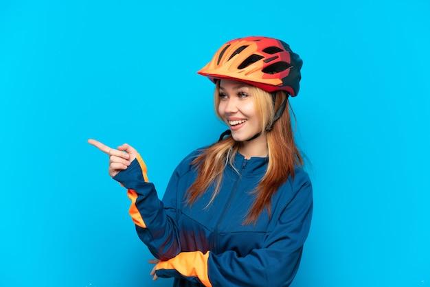 Молодая велосипедистка изолирована на синем фоне, указывая пальцем в сторону и представляет продукт