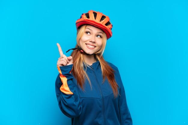 素晴らしいアイデアを指している青い背景に分離された若いサイクリストの女の子