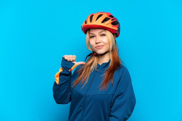 Молодая велосипедистка изолирована на синем фоне, гордая и самодовольная