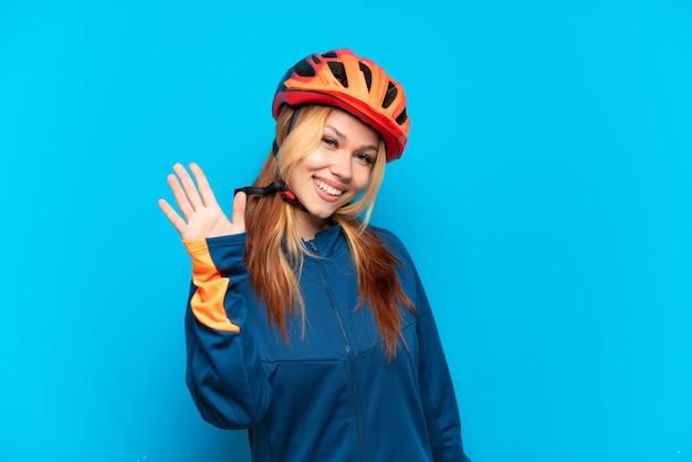 幸せな表情で手で敬礼青い背景で隔離の若いサイクリストの女の子