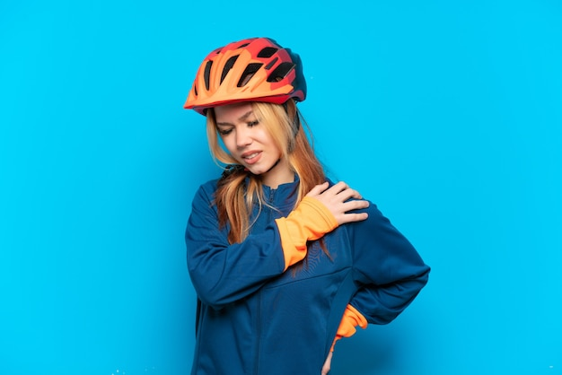 努力したために肩の痛みに苦しんでいる青い背景で隔離の若いサイクリストの女の子