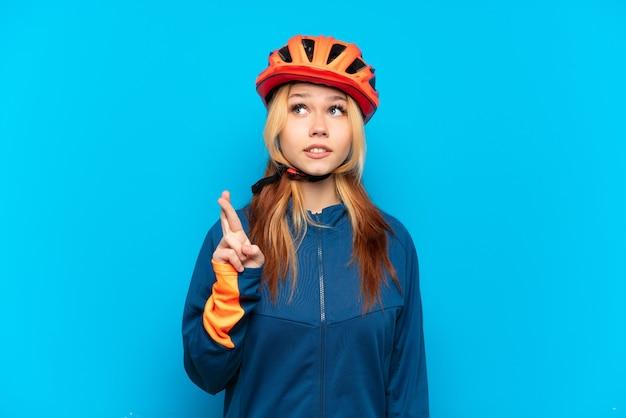 Молодая велосипедистка изолирована на синем фоне со скрещенными пальцами и желает лучшего