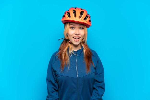 Молодая велосипедистка изолирована на синем фоне с удивленным выражением лица