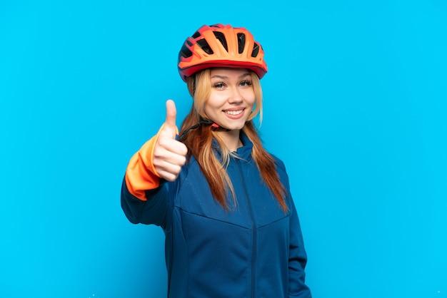 Молодая велосипедистка изолирована на синем фоне с большими пальцами руки вверх, потому что произошло что-то хорошее