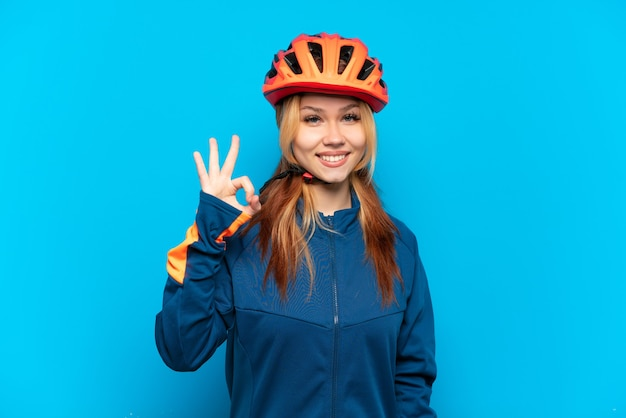 Young cyclist girl isolated showing ok sign with fingers
