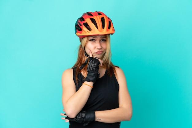 Девушка молодой велосипедист на изолированном синем фоне и мышления Premium Фотографии