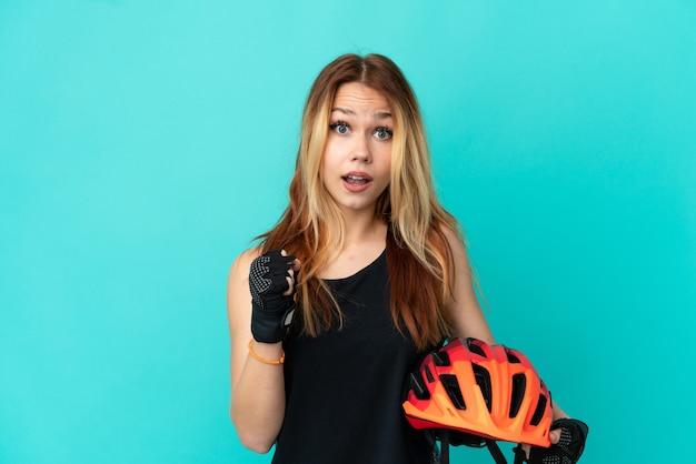 Молодая велосипедистка на изолированном синем фоне празднует победу в позиции победителя