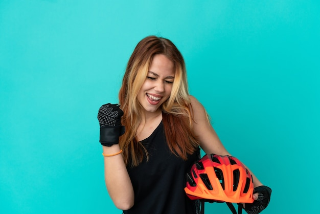 Девушка молодой велосипедист на изолированном синем фоне празднует победу