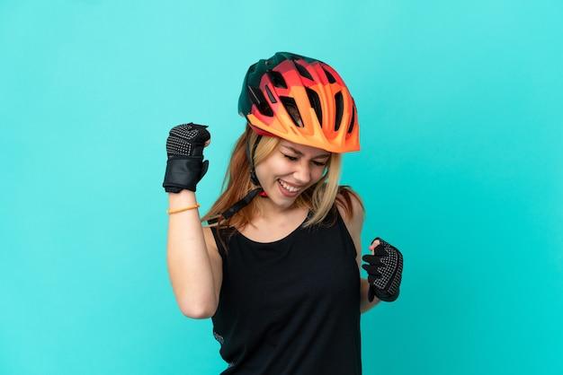 Молодой велосипедист девушка на изолированном синем фоне празднует победу