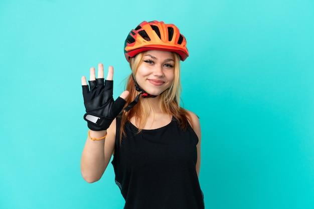 Молодая велосипедистка на изолированном синем фоне, считая пять пальцами
