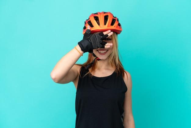 Молодой велосипедист девушка на изолированном синем фоне, закрывая глаза руками и улыбаясь