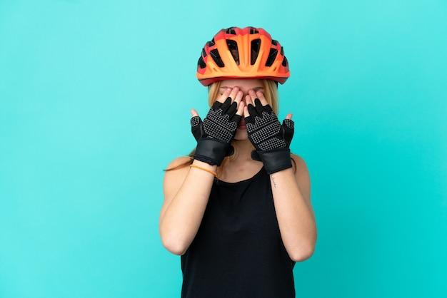 Молодой велосипедист девушка на изолированном синем фоне, закрывая глаза руками