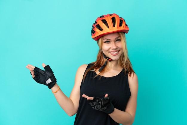 Молодая велосипедистка на изолированном синем фоне, протягивая руки в сторону, приглашая приехать