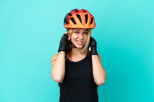 Молодая велосипедистка на изолированном синем фоне расстроена и закрывает уши