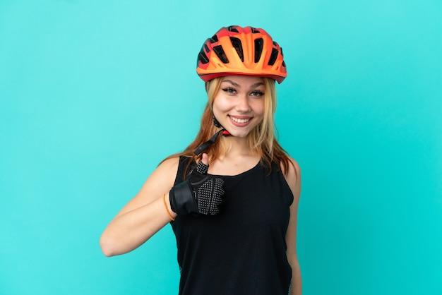 Молодая девушка-велосипедист на изолированном синем фоне показывает палец вверх жестом Premium Фотографии