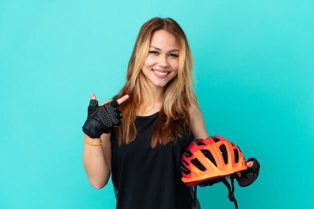 Молодая девушка-велосипедист на изолированном синем фоне показывает палец вверх жестом