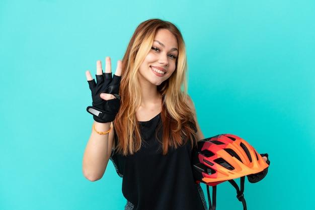 고립된 파란색 배경 위에 있는 어린 자전거 타는 소녀는 행복하고 손가락으로 4를 세고 있습니다.