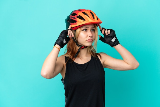 Молодая велосипедистка на изолированном синем фоне с сомнениями и мышлением