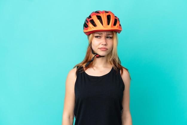 Молодой велосипедист девушка на изолированном синем фоне, сомневаясь, глядя в сторону