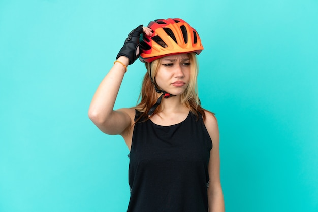 Молодой велосипедист девушка на изолированном синем фоне, сомневаясь, почесывая голову