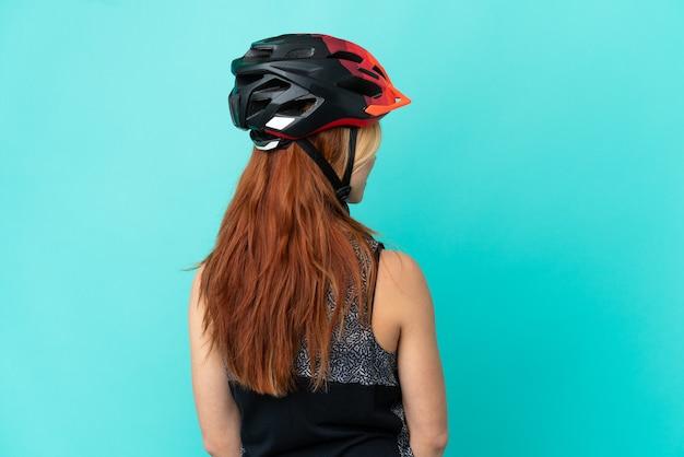 Молодая велосипедистка на изолированном синем фоне в заднем положении и смотрит в сторону