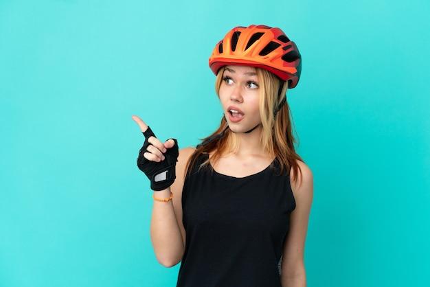Молодая велосипедистка на изолированном синем фоне, намереваясь реализовать решение, подняв палец вверх