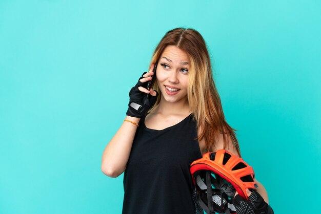 Молодая велосипедистка на изолированном синем фоне, разговаривая с кем-то по мобильному телефону