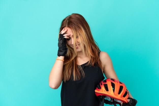 Девушка молодой велосипедист на изолированном синем фоне смеется
