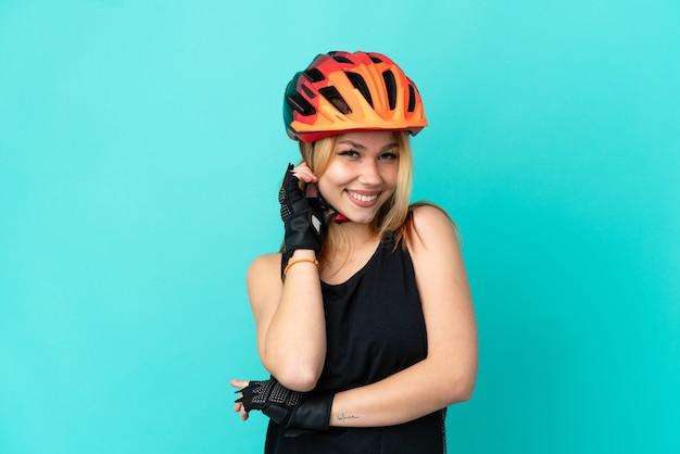 Девушка молодой велосипедист на изолированном синем фоне смеется Premium Фотографии