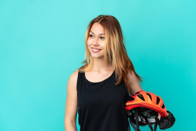 Девушка молодой велосипедист на изолированном синем фоне, глядя в сторону