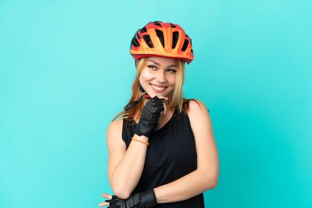 Молодой велосипедист девушка на изолированном синем фоне смотрит в сторону и улыбается