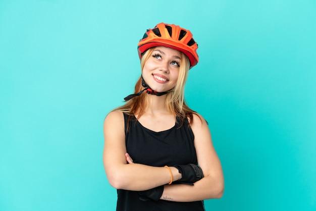 Молодая велосипедистка на изолированном синем фоне, глядя вверх, улыбаясь Premium Фотографии