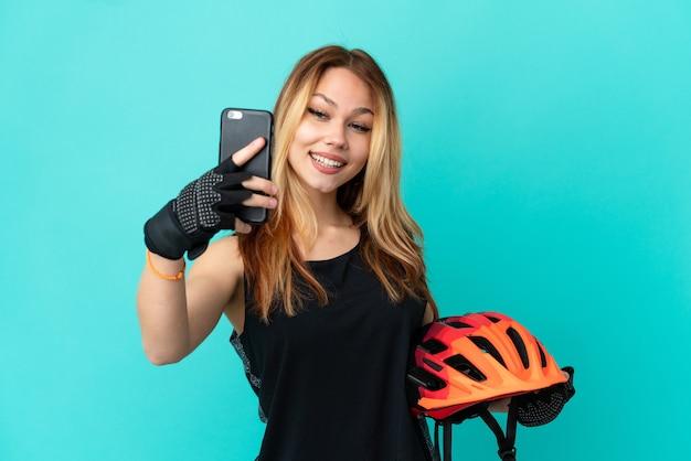 Девушка молодой велосипедист на изолированном синем фоне, делая селфи