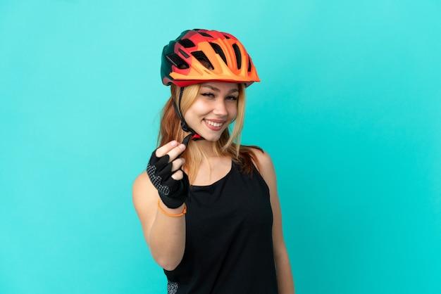 Девушка молодой велосипедист на изолированном синем фоне, делая денежный жест Premium Фотографии