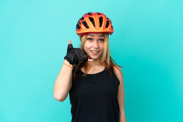 Девушка молодой велосипедист на изолированном синем фоне, делая телефонный жест. перезвони мне знак Premium Фотографии