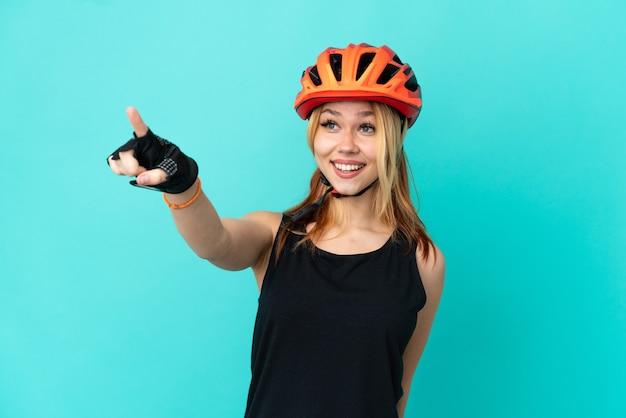 Девушка молодой велосипедист на изолированном синем фоне, указывая в сторону