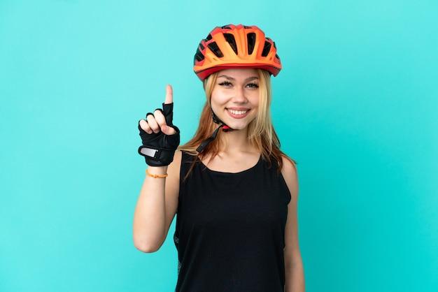 Молодая велосипедистка на изолированном синем фоне, указывая на отличную идею