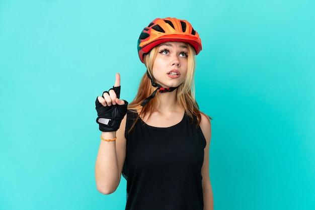Молодой велосипедист девушка на изолированном синем фоне, указывая вверх и удивлен