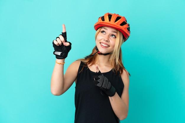 Молодая велосипедистка на изолированном синем фоне, указывая указательным пальцем, отличная идея