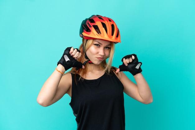 Молодая велосипедистка на изолированном синем фоне гордая и самодовольная