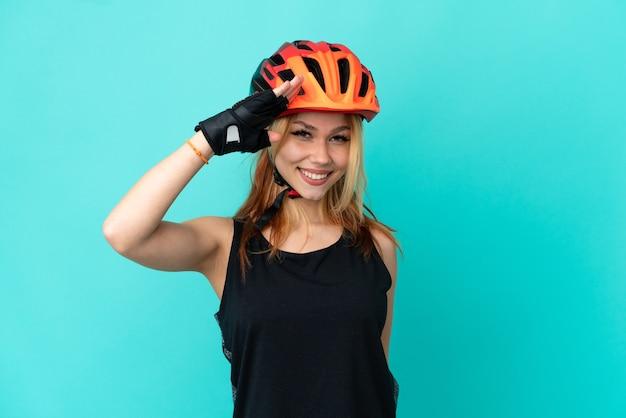 Молодая велосипедистка на изолированном синем фоне, салютуя рукой с счастливым выражением лица