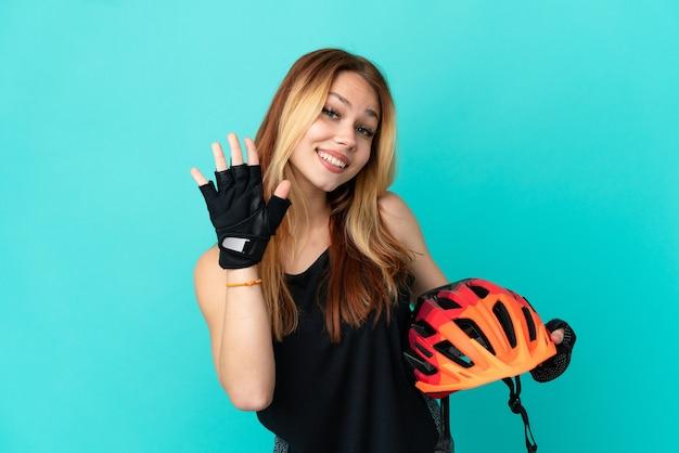 행복한 표정으로 손으로 경례하는 고립된 파란색 배경 위에 젊은 사이클 소녀
