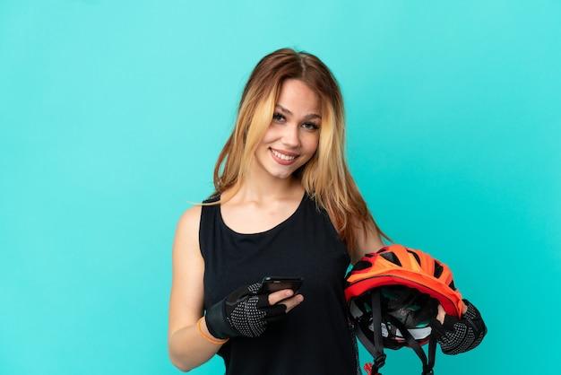 Молодая велосипедистка на изолированном синем фоне, отправив сообщение с мобильного телефона