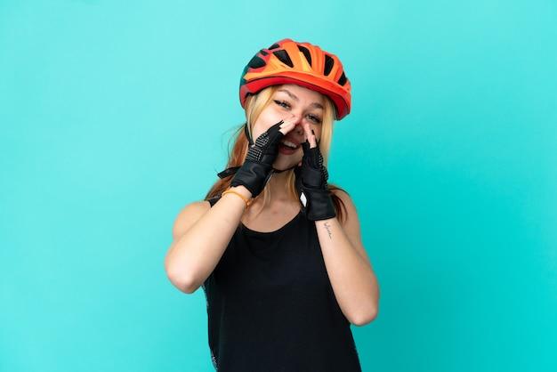 Молодая велосипедистка на изолированном синем фоне кричит и что-то объявляет