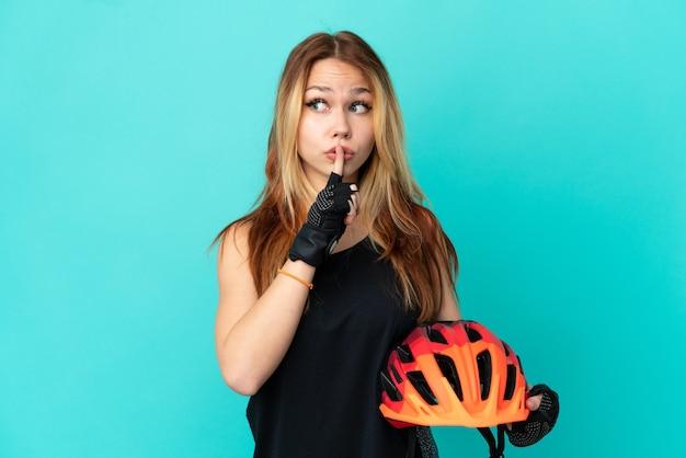 Молодая велосипедистка на изолированном синем фоне показывает знак жеста молчания, кладя палец в рот