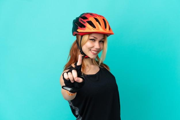Молодая велосипедистка на изолированном синем фоне показывает и поднимает палец Premium Фотографии